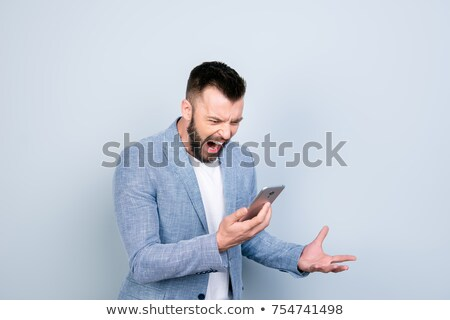 Businessman grimacing at his phone Stock photo © photography33