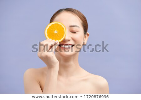 Young girl holding orange slices in front of her eyes Stock photo © photography33