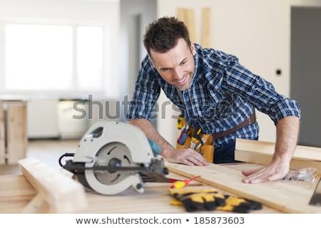 Stock photo: Construction worker examining his circular saw.