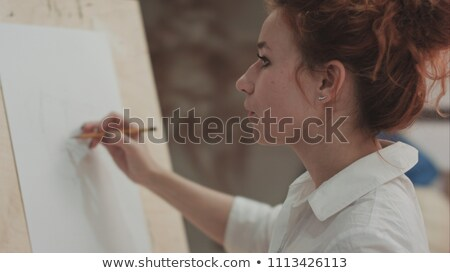 happy woman artist making sketches on canvas in art class stock photo © deandrobot