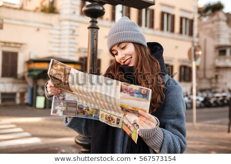 Stock photo: Smiling concetrated woman using map and walking in city