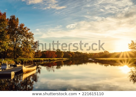 serene view of calm lake and sunset clouds stock photo © juhku