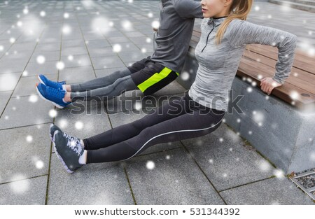 couple of sportsmen doing triceps dip on bench Stock photo © dolgachov