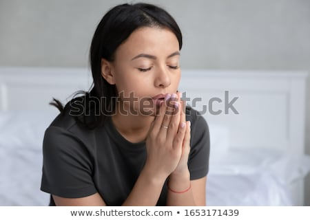 Stock photo: Woman praying with joining hands and eyes closed