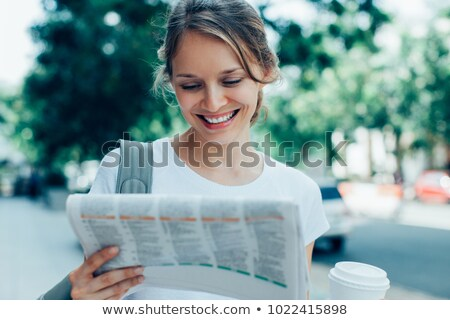Smiling businesswoman holding disposable cup reading newspaper Stock photo © wavebreak_media