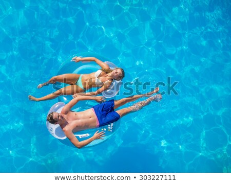 Man on inflatable lilo in pool Stock photo © IS2
