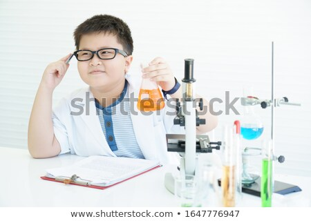 Little caucasian boy holding test tube and beaker. Stock photo © RAStudio