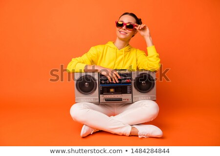 Portrait of a happy girl sitting on a boombox Stock photo © deandrobot