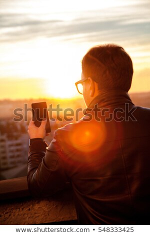 Man standing on balcony using phone Stock photo © IS2