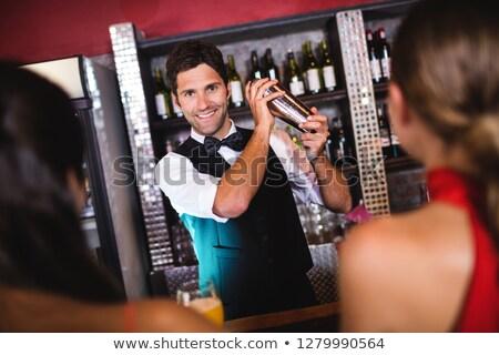 smiling man shaking a cocktail stock photo © kzenon
