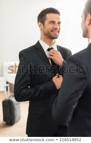 Smiling businessman adjusting his necktie Stock photo © Minervastock