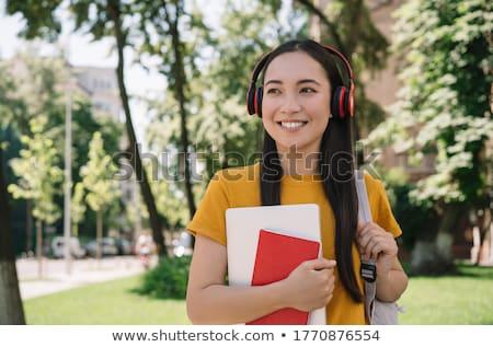 Gyönyörű fiatal nő fülhallgató áll kint utca Stock fotó © deandrobot