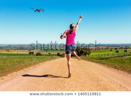 Woman leaping for joy along dirt road flying a drone Stock photo © lovleah