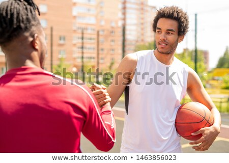 Young intercultural sportsman with ball shaking hand of his playmate Stock photo © pressmaster