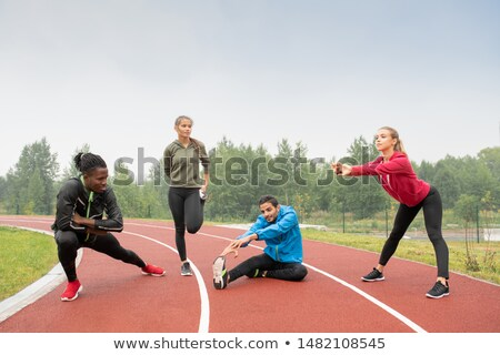 Young healthy intercultural men and women in sportswear doing physical exercises Stock photo © pressmaster