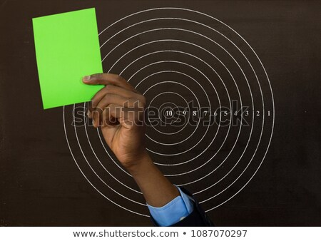 Сток-фото: Hand Holding Green Card In Front Of Circle Radius Numbers