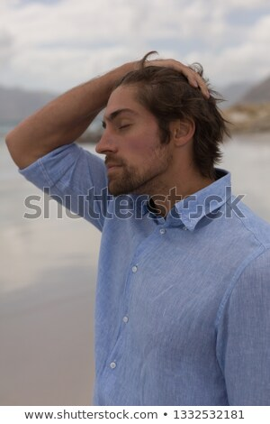 Side view of worried man revitalizing and standing on the beach with eyes closed Stock photo © wavebreak_media