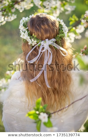 A girl in a light long white dress with a wreath on her head and barefoot on a forest path crosses t Stock photo © ElenaBatkova