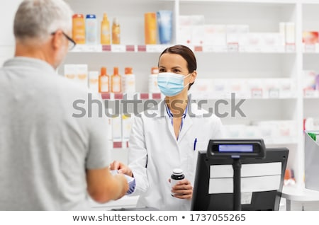 apothecary with cure and customer at pharmacy Stock photo © dolgachov