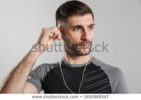 Image of brutal unshaven sportsman posing and using earphones Stock photo © deandrobot