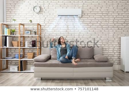Feliz mujer acondicionador de aire remoto control remoto Foto stock © AndreyPopov