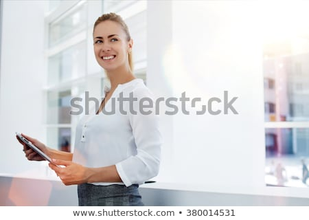 smiling young business woman using tablet pc while standing rela stock photo © hasloo