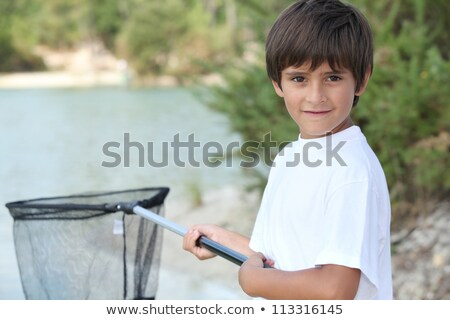 Little boy at a riverside with a landing net Stock photo © photography33
