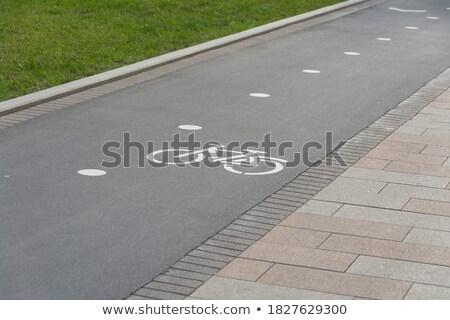 white cycle lane sign on paving slabs stock photo © latent