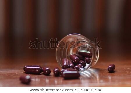 Spilled tablets and medicine bottle. Tablets on a green backgrou Stock photo © Tatik22