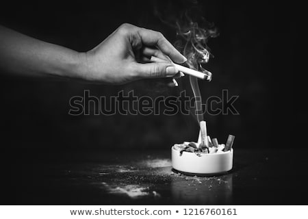 Stock photo: Ash of cigarette against a black background