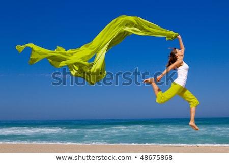 Boldog fiatal nő ugrik tengerpart égbolt víz Stock fotó © rozbyshaka