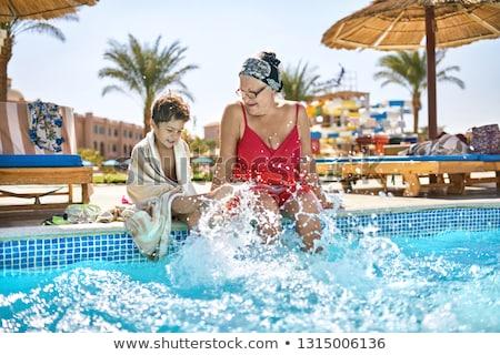La grand-mère et les enfants s'assoient à la piscine Photo stock © bezikus