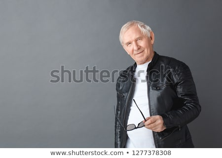 mature man in leather jacket standing in gray studio Stock photo © feedough