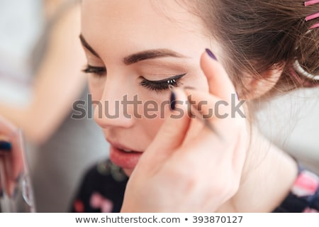 Makeup artist doing false lashes to young woman in curlers Stock photo © deandrobot