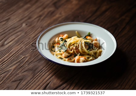 Pasta with shrimps and tomato sauce on dark wooden background.  Stock photo © Yatsenko