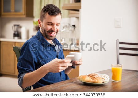 handsome young man having breakfast stock photo © deandrobot