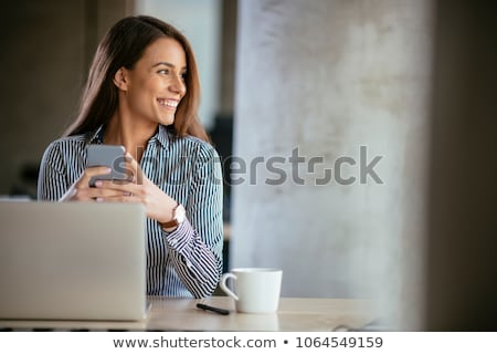 woman with laptop calling on smartphone at office Stock photo © dolgachov