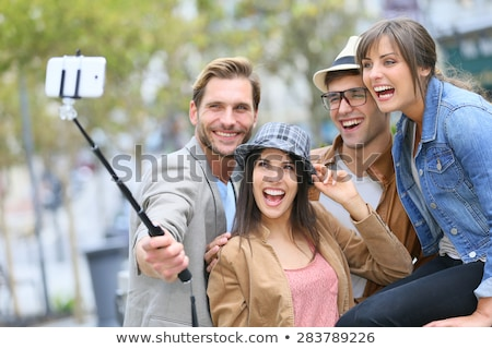 friends taking picture by selfie stick at summer Stock photo © dolgachov