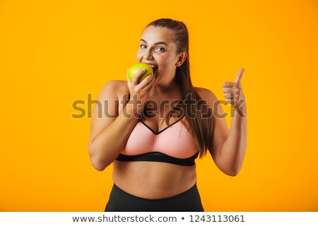 Portrait of adult chubby woman in sportive bra eating apple, iso Stock photo © deandrobot