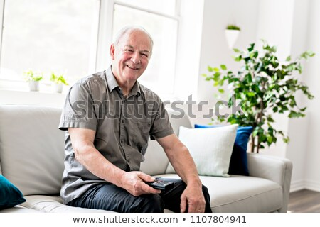 Senior man at home watching tv wiith remote control Stock photo © Lopolo