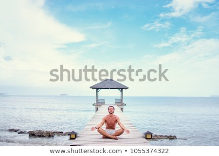handsome young sports man on the beach meditate outdoors stock photo © deandrobot