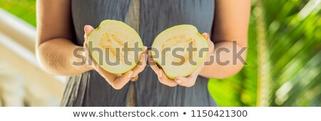 guava in beautiful female hands on a green background. BANNER, long format Stock photo © galitskaya