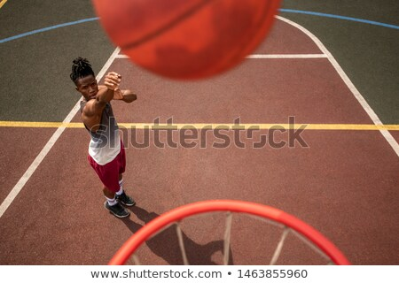 African young sportsman throwing ball in basket while standing on the court Stock photo © pressmaster