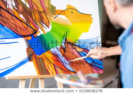 Part of abstract painting on sheet of paper and hand of artist with paintbrush Stock photo © pressmaster