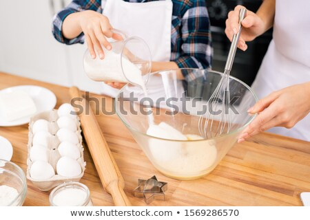 Little child sugar into bowl with shaked raw eggs while helping his mom Stock photo © pressmaster