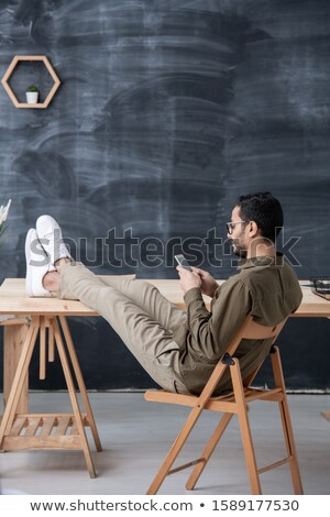 Young casual employee keeping legs on table while scrolling in smartphone Stock photo © pressmaster