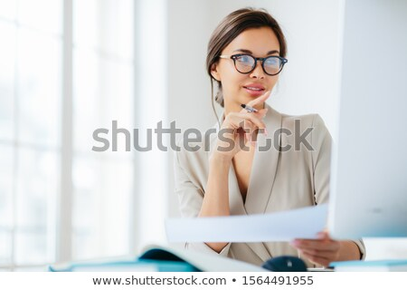 Female economist poses in coworking space, focused in monitor, verifies or checks figures from finan Stock photo © vkstudio