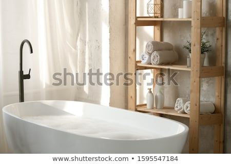 Large porcelain white bathtub filled with water and foam by wooden shelves Stock photo © pressmaster