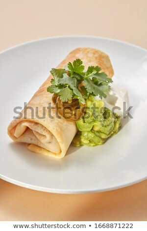 Homemade pancake roll with spicy guacamole and white sauces. Stock photo © artjazz