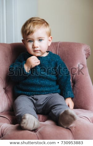 Cute little child with plump cheeks, blonde hair, wears fashionable clothes, sits on armchair, has c Stock photo © vkstudio